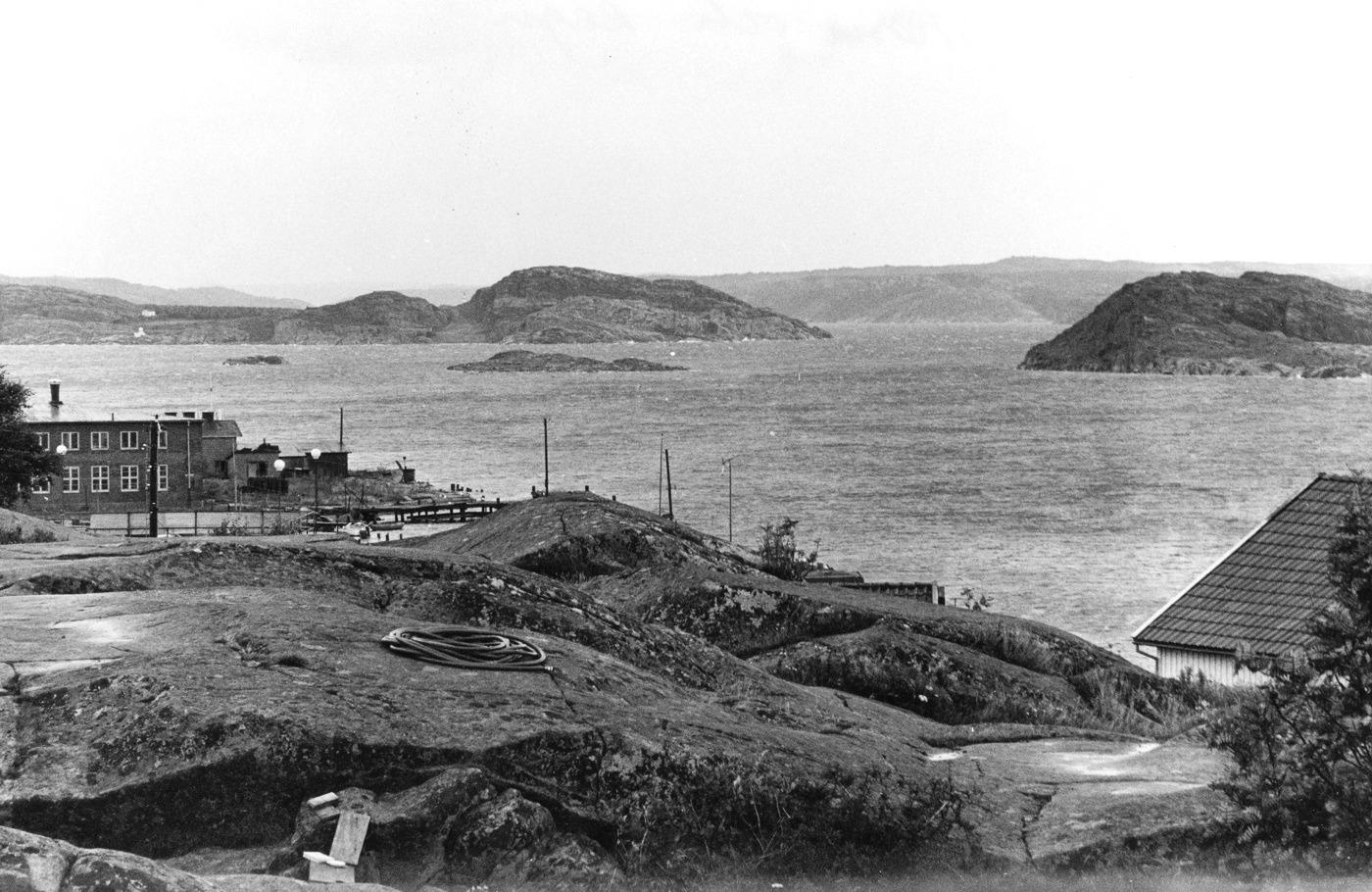 Foto Claea Funck 1968. Vy mot konservfabriken och Åbyfjordens mynning med berg nedanKanpes hus i förgrunden.