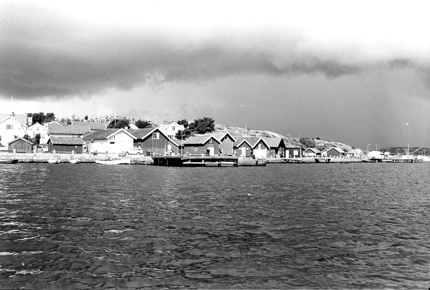 """Foto Claes Funck 1968. Sjöbodar, ångbåtsbrygga och Thores livs från sjön.  Längst till höger Grönvik med utskeppningskaj och huggeri av kant- och gatsten, sk """"knott""""."""