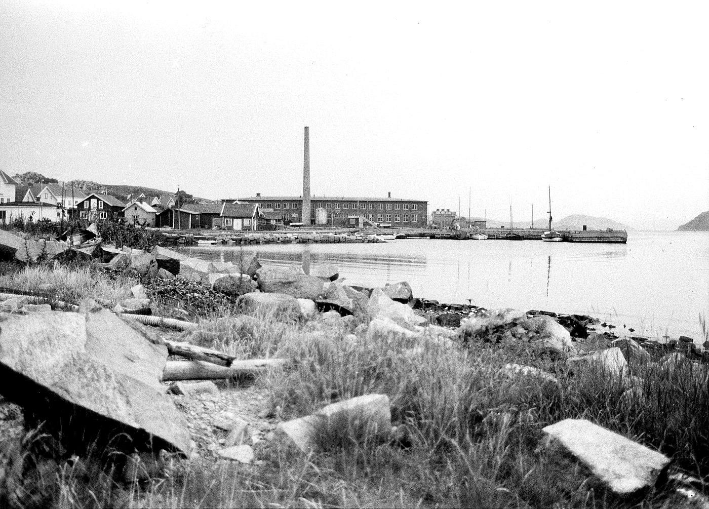 Foto Claes Funck 1963. Konservfabriken med skorsten ca 25m hög. Ångbåtsbrygga går ut i vattnet och hitom den Bäckebryggan. Vitt hus längst till vänster är Holmbergs Pensionat, idag plats för Centrumhuset. Taget från Rompesand, nu minigolfbana.