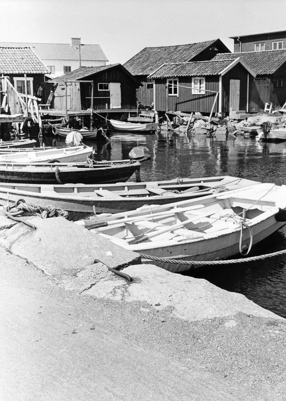Foto Claes Funck 1968. Bodar och ekor vid Norra Bäckebryggan. Amandus Karlssons sjöbod är den med vit dörr och den vita ekan ligger förtöjd vid Amundus brygga.