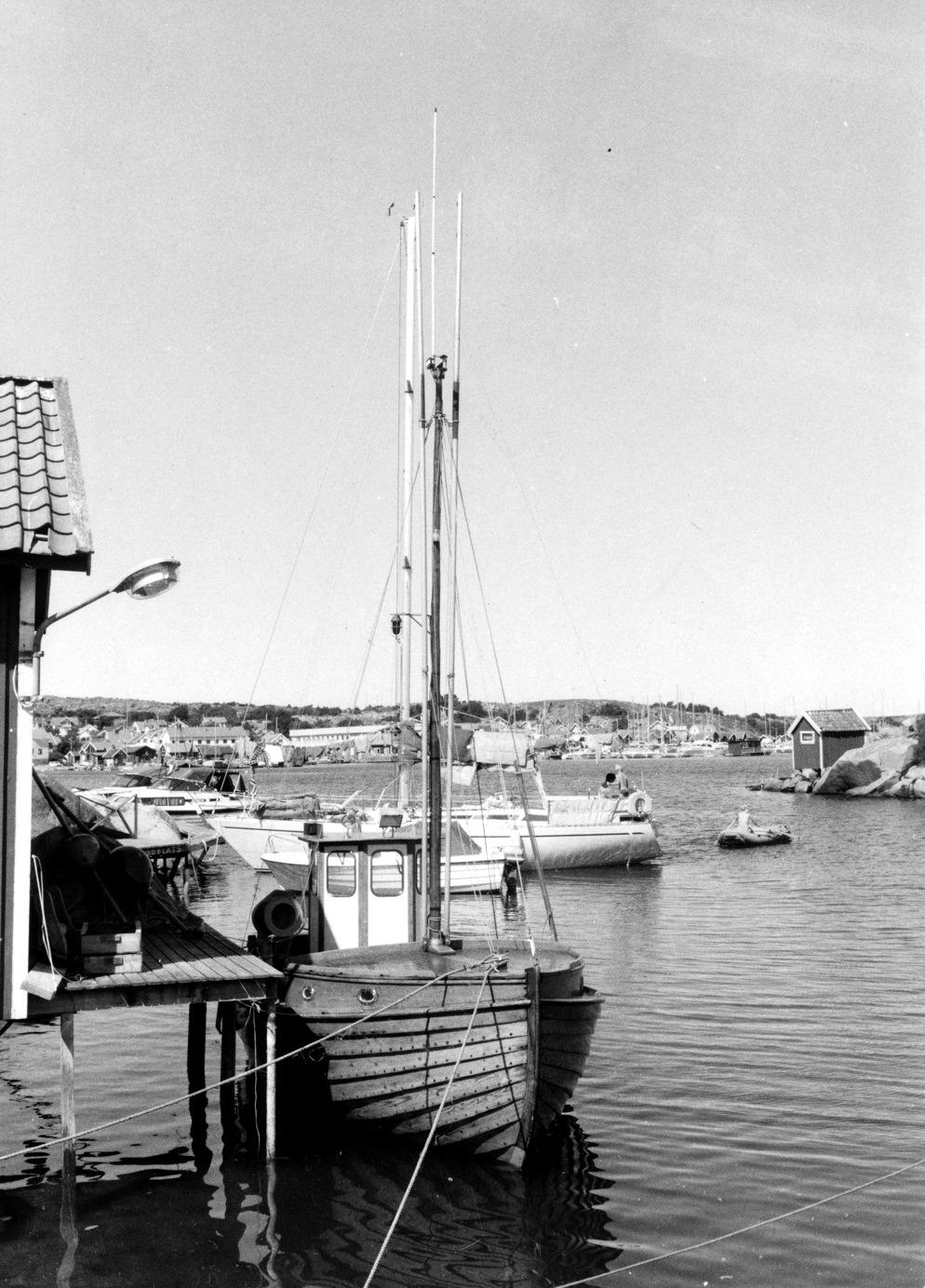 """Foto Claes Funck 1984. Vy över fiskebåt mot samhället. Sivars son ärvde hus och brygga - här hans """"julle""""."""