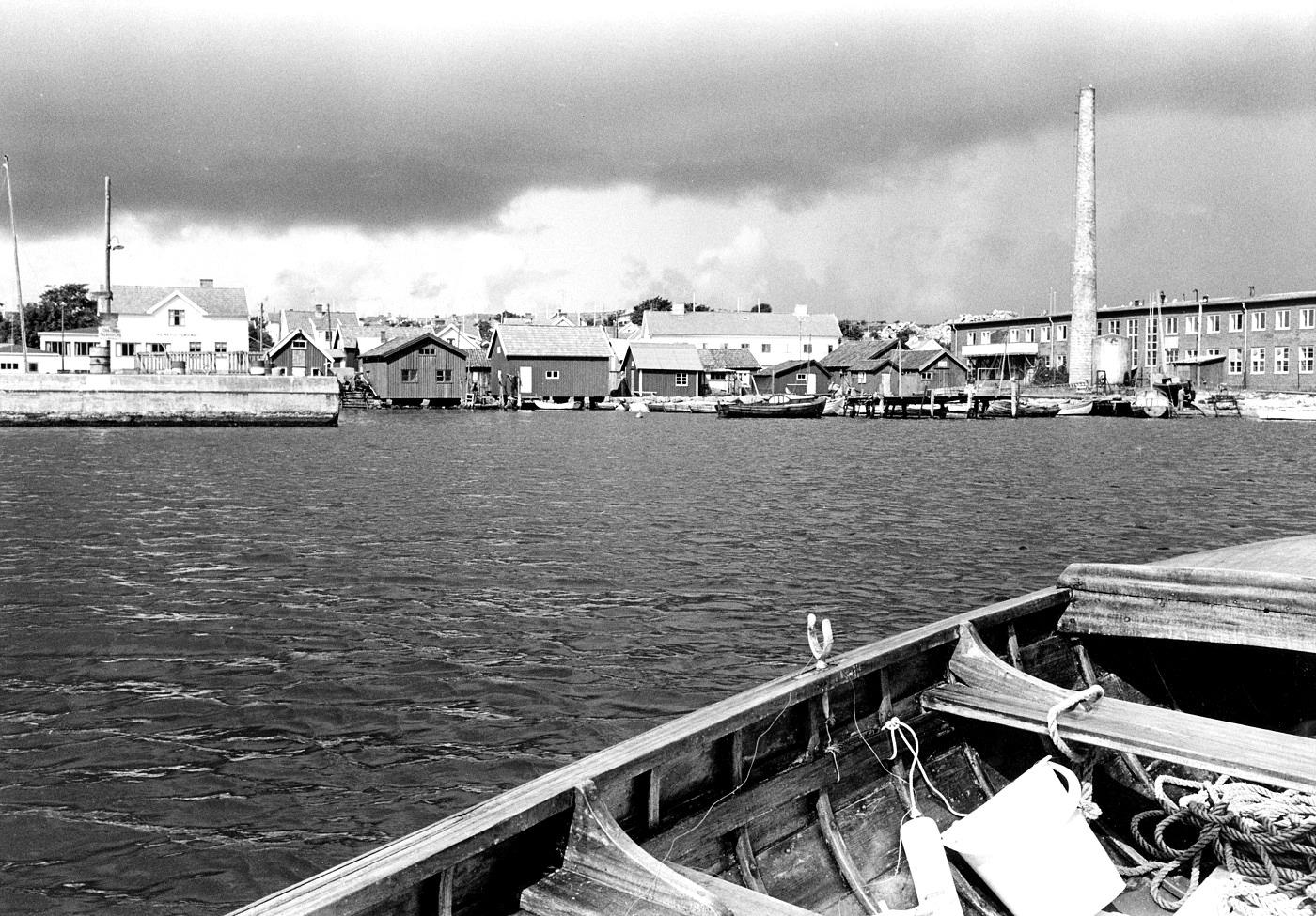 """Foto Claes Funck 1965. Fr vänster ångbåtsbrygga med Holmbergs Pensionat, sjöbodar och Konsum, till höger konservfabriken """"Sjömärket""""."""