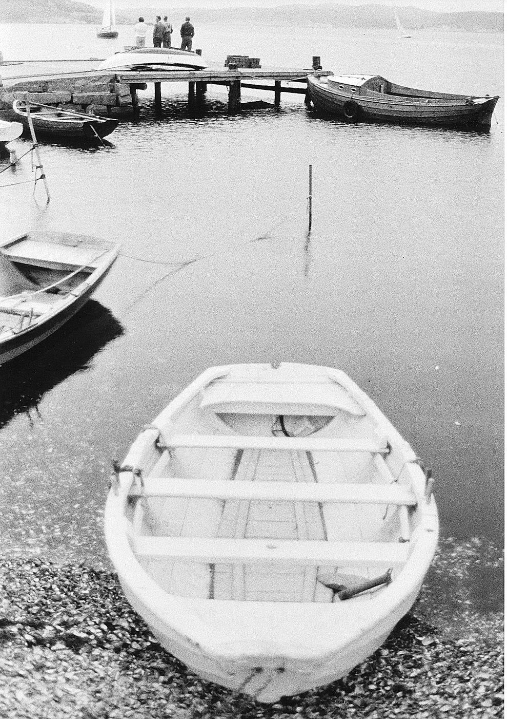 """Foto Claes Funck 1963. Vit eka på strand vid ångbåtsbryggan. """"Skäl"""", dvs blåmusselskal täcker stränderna nordväst om konservfabriken SJÖMÄRKET. Blåmusslor utifrån havet köptes och kokades. Skalen, med pärlemor på insidan, kastades på stränderna. Detta är en lånad eka av Amundus Karlsson som dragits upp på stranden vid pensionatet. Sedermera täcktes stranden av sten från stenhuggeriet."""